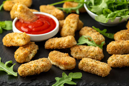 Fried mozzarella cheese sticks in breadcrumbs with ketchup sauce and wild rocket leaves 写真素材