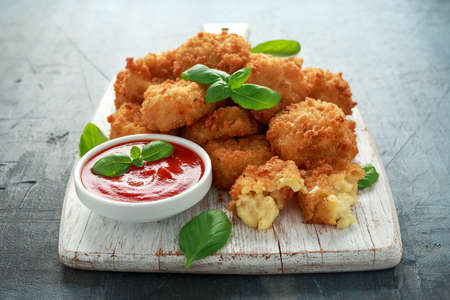 Fried Mac, macaroni and Cheese Bites in breadcrumbs with ketchup sauce on white wooden board