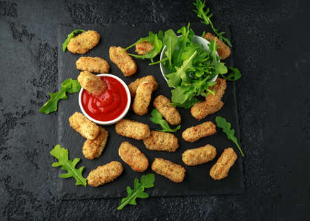 Fried mozzarella cheese sticks in breadcrumbs with ketchup sauce and wild rocket leaves.