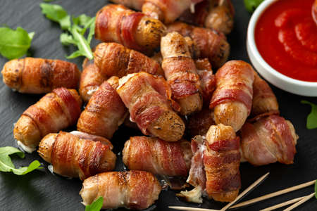 Party finger food pigs in blankets on toothpicks with ketchup sauce and wild rocket leaves.
