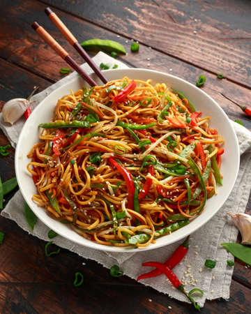 Chow mein, noodles and vegetables dish with wooden chopsticks Stock Photo