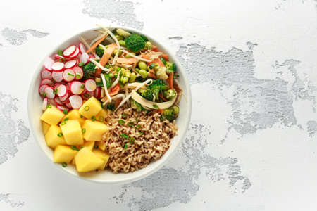 Asian style Vegan salad bowl with edamame, vegetable stir-fry mix, wholegrain rice, quinoa, mango chunks drizzled with mango, chilli dressing
