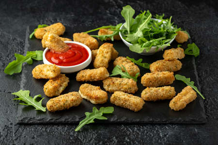 Fried mozzarella cheese sticks in breadcrumbs with ketchup sauce and wild rocket leaves 스톡 콘텐츠
