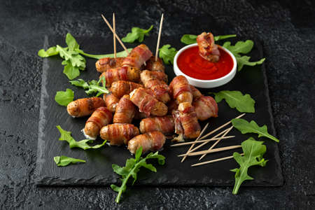 Party finger food pigs in blankets on toothpicks with ketchup sauce and wild rocket leaves Reklamní fotografie