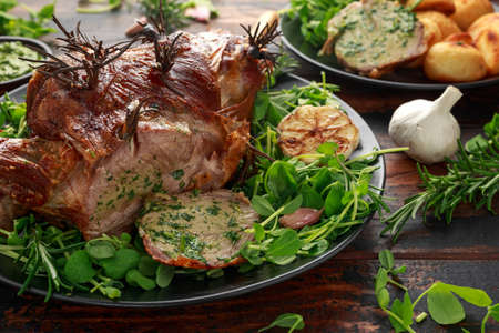 Roast Lamb leg with mint sauce, rosemary and garlic. on black plate, wooden table 写真素材