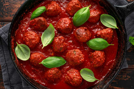 Homemade Meatballs in iron cast with sweet and hot tomato sauce, basil. On wooden table