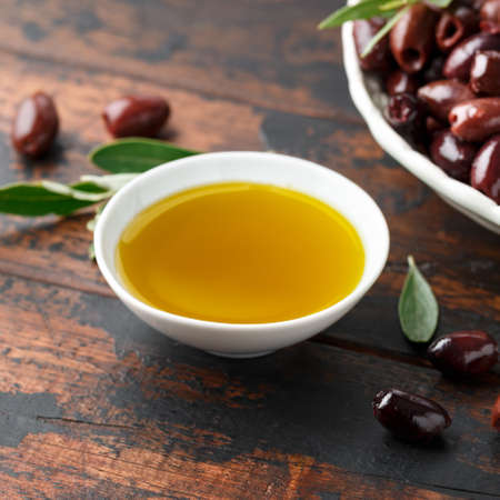 Extra virgin olive oil and kalamata olives on rustic wooden background Stok Fotoğraf