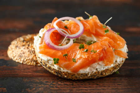 Bagels breakfast sandwich with Cream cheese and salmon on wooden table Imagens