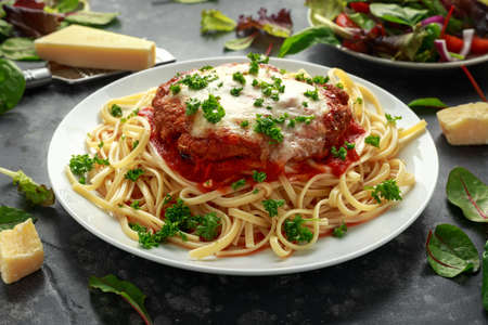 Chicken Parmesan with Cheese and Marinara Sauce served over spaghetti, pasta.