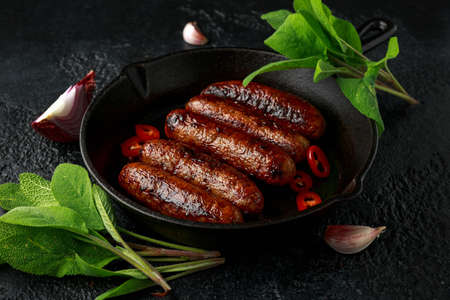 Butcher made sage and onion sausages baked in cast iron skillet, pan