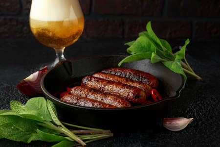 Butcher made sage and onion sausages baked in cast iron skillet, pan and glass of cold beer