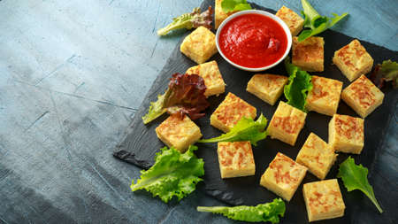 Spanish Potato Frittata tapas with tomato sauce on stone board
