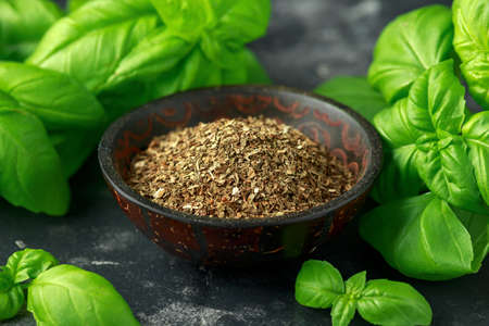 Fresh and dried basil in bowl. on black rustic table