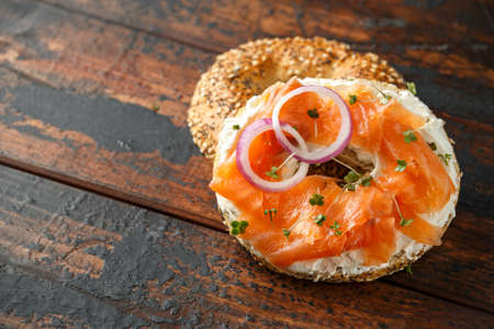 Bagels breakfast sandwich with Cream cheese and salmon on wooden table. Imagens