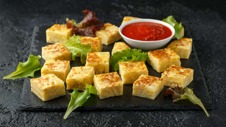 Spanish Potato Frittata tapas with tomato sauce on stone board.