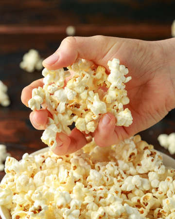 Hand takes salty popcorn from the bowl.