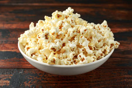 bowl of salty popcorn on wooden table