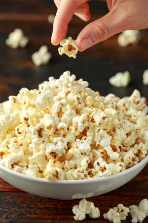 Hand takes salty popcorn from the bowl