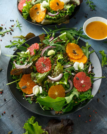 Orange and grapefruit Citrus salad with lentills vertes, wild rocket, arugula, red onion and sprinkle of pumpkin seeds. 版權商用圖片