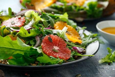 Orange and grapefruit Citrus salad with lentills vertes, wild rocket, arugula, red onion and sprinkle of pumpkin seeds. Фото со стока