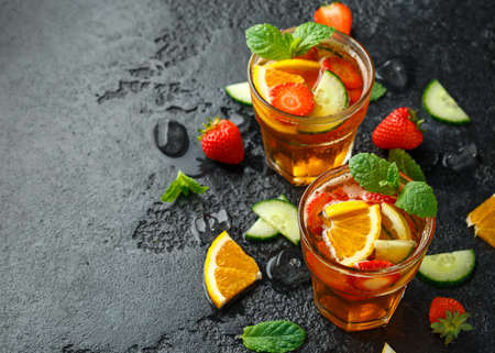 Refreshing Pimms Cocktail with Fruit and vegetables on rustic black table. Imagens