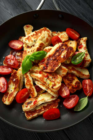 Pan-seared halloumi cheese and sweet cherry tomatoes salad Archivio Fotografico