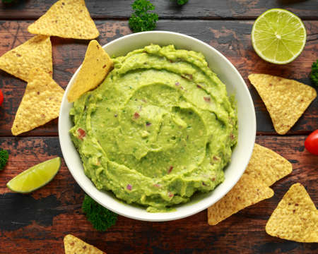 Bowl of fresh Guacamole with nachos chips and herbs. Healthy Vegan, Vegetables food.