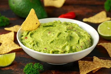 Ciotola di guacamole fresco con nachos ed erbe aromatiche. Vegano sano, cibo a base di verdure
