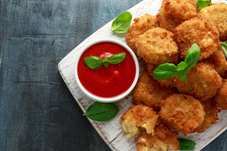 Fried Mac, macaroni and Cheese Bites in breadcrumbs with ketchup sauce on white wooden board. Stock Photo