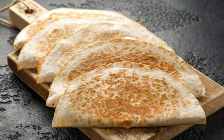 Mexican food quesadillas with chicken and cheese served on rustic wooden chopping board.