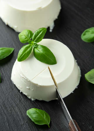 Fresh Ricotta cheese with basil leaf on black rustic table. selected focus Stock Photo