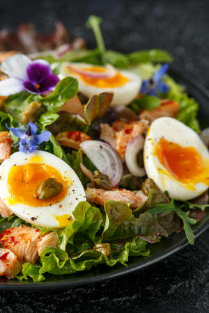 Smoked salmon and jammy soft-boiled free range egg and capers salad with edible borage and pansy flowers. Stock Photo