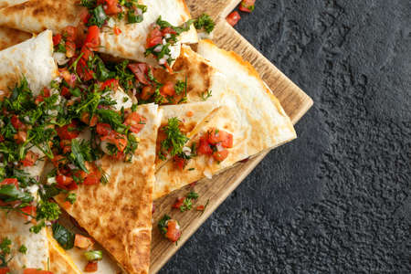 Mexican food quesadillas with chicken and cheese served on rustic wooden chopping board with homemade fresh salsa topping.