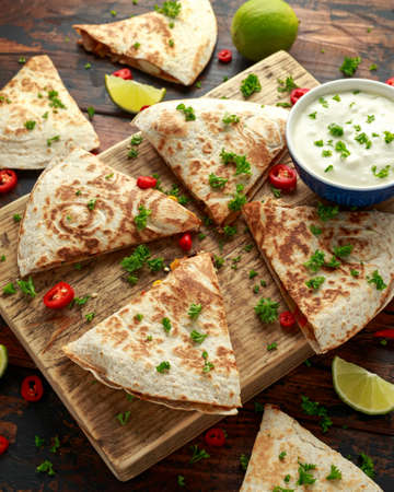 Mexican quesadilla with chicken, corn, black beans, cheese, vegetables, lime and yogurt sauce on wooden board.