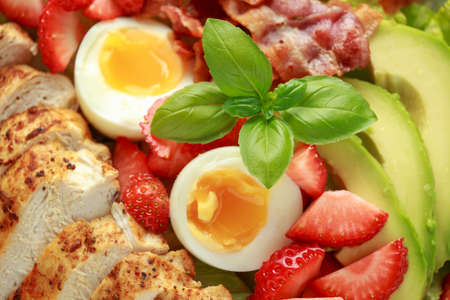 Chicken Cobb salad with strawberries, bacon, avocado and boiled eggs.