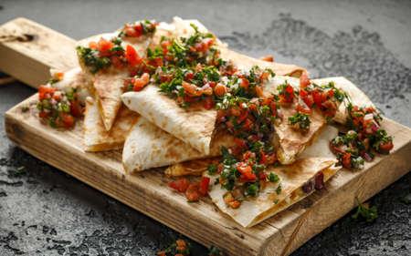 Quesadillas de comida mexicana con pollo y queso servido en una tabla de cortar de madera rústica con aderezo de salsa fresca casera Foto de archivo