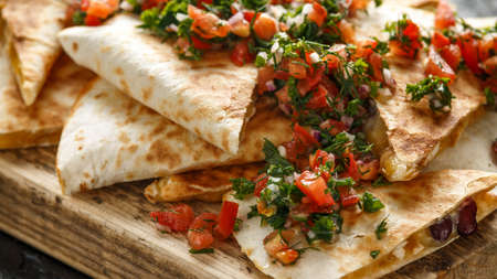 Mexican food quesadillas with chicken and cheese served on rustic wooden chopping board with homemade fresh salsa topping