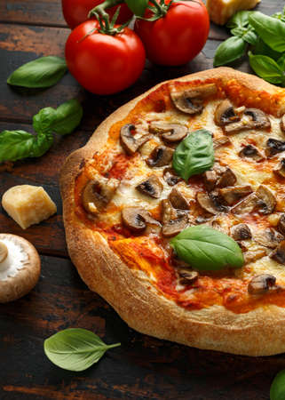 Hot Mushroom Pizza with basil, tomatoes, mozzarella and parmesan cheese on wooden table. ready to eat. vegetarian food
