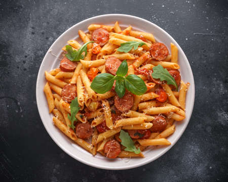 Sausage penne Pasta with tomato sauce and fresh herbs Фото со стока