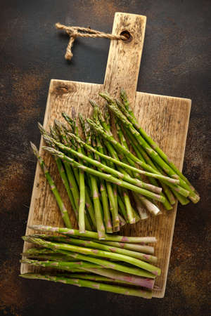 Freshly picked organic asparagus on wooden board