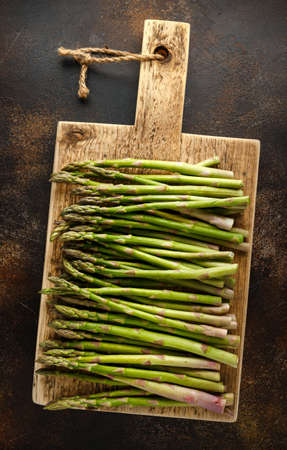 Freshly picked organic asparagus tips on wooden board