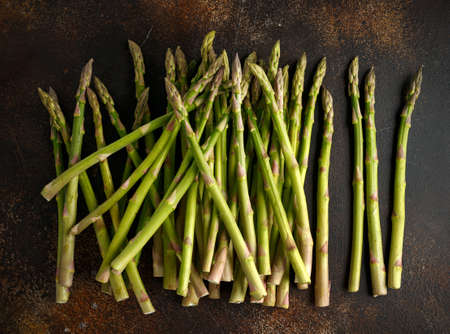 Freshly picked organic asparagus tips on brown table