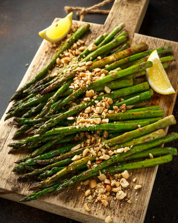 Fried asparagus tips served with crispy crushed peanuts on wooden board