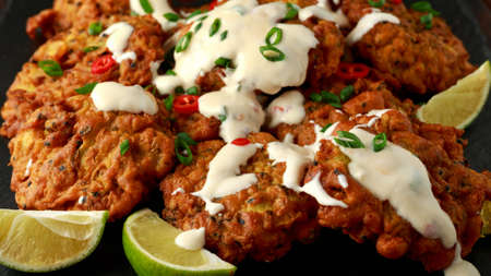 Indian takeaway food, spicy onion bhajis served with chili yoghurt dip and lime wedges on wooden board
