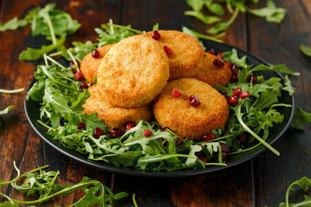 Thai food spicy fish cakes served with pomegranate seeds and wild rocket, arugula salad.