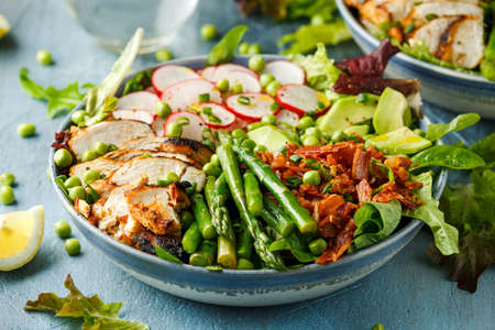 Cobb salad bowl with grilled chicken breast, asparagus, avocado, radishes and bacon 写真素材