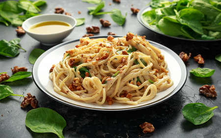 Pasta with roasted walnut, ricotta white pesto sauce, parmesan cheese and spinach