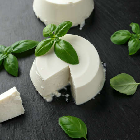 Fresh Ricotta cheese with basil leaf on black rustic table