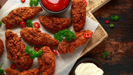 Breaded chicken strips with beer, ketchup and mayonnaise on wooden board Reklamní fotografie
