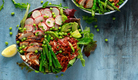 Cobb salad bowl with grilled chicken breast, asparagus, avocado, radishes and bacon Stock Photo